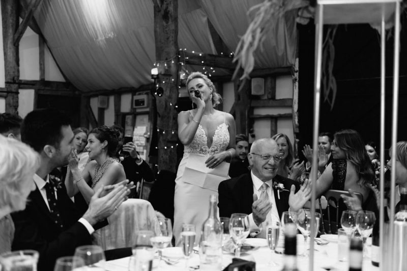 bride giving a speech at a feminist wedding surrounded by friends and family at South Farm