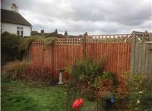 Replaced fence damaged by high winds and removed tree.
