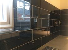 Glass tiles installed in the kitchen including windows shelf area and back splash for hob.