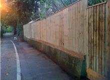 Erect 22m of six ft feather board fence on concrete retaining wall and garden gate.