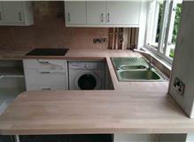 Fitting new u shaped wooden work surface.