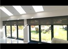 Two electric roller blinds for by fold doors, 3.1m wide powered by Somfy mains motors.