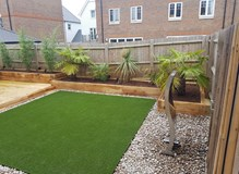 New timber deck and raised planters with artificial  lawn