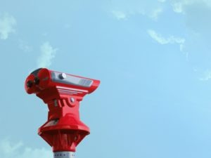 Red telescope against a blue sky