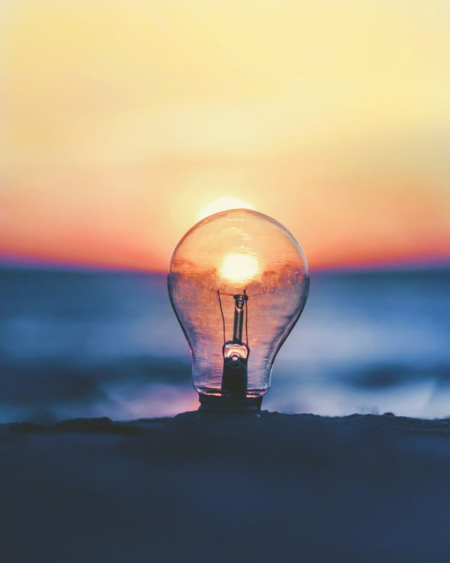 Lightbulb in front of a sunset - Photo by Ameen Fahmy