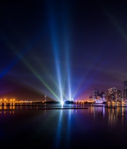 Lights projected from a building by the water