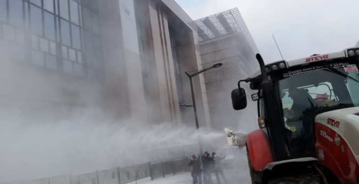 Pics: Farmers coat EU Council buildings with milk powder in protest