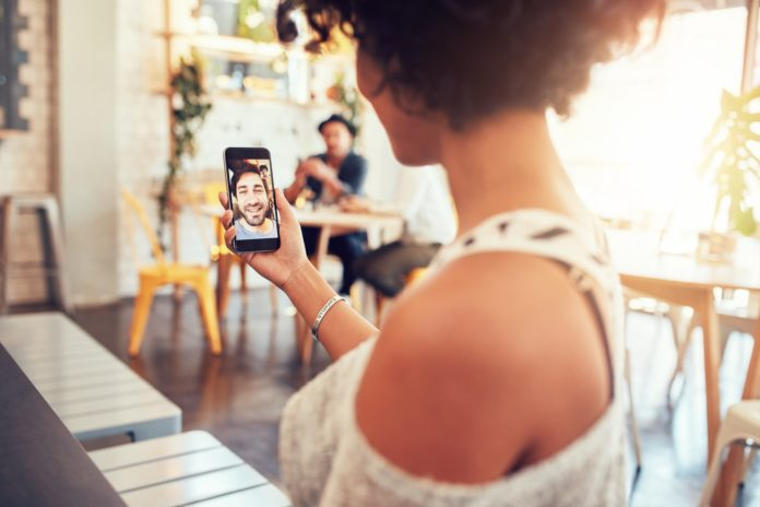 Woman having a videochat with man on mobile phone.