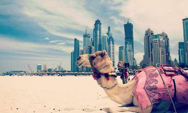Cloudy skies over a camel lying on the sand and the stunning Dubai skyline. Explore Dubai Hen Party ideas below: