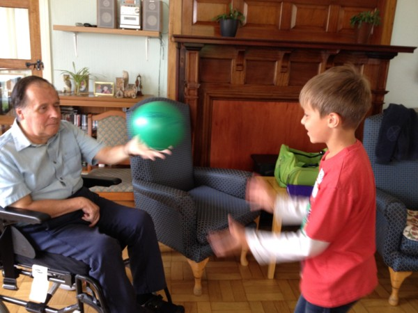 Image of Natasha's son playing catch with a stroke client on 'take your kid to work day' at Eryl Fryn Care Home in Llandudno 2016