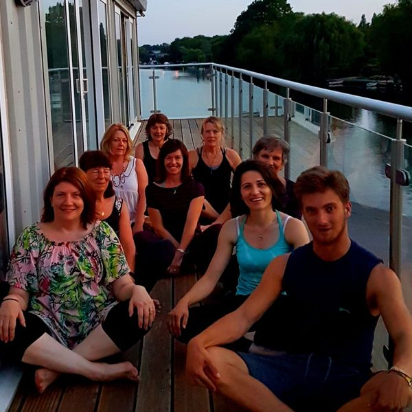Yoga class at the end of the class on the veranda by the beautiful river