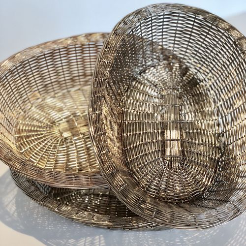 Three rustic French woven metal bread baskets