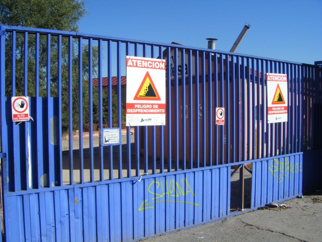 Foto 47.- 7 de octubre. Carteles de peligro de desprendimiento en las puertas del taller y ampliado el agujero inicialmente abierto en la chapa
