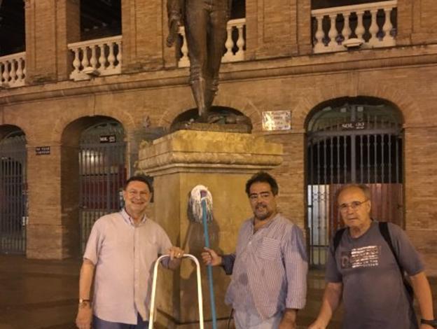 Ortiz, en el centro tras limpiar la estatua de Montoliu.Foto de Eduardo Osca