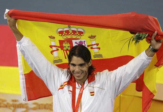 FILE - In this Aug. 17. 2008 file photo, Rafael Nadal of Spain celebrates his gold medal with his national flag following his singles finals match against Fernando Gonzalez of Chile during the Beijing 2008 Olympics in Beijing. Rafael Nadal will be Spain's flag-bearer at the Rio de Janeiro Olympics. The announcement was made Wednesday, April 27, 2016, at an event in Madrid marking the 100-day countdown to the Aug. 5 opening ceremony at Rio's Maracana Stadium. (AP Photo/Charles Krupa, File)