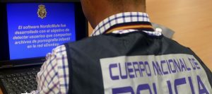 Un agente de Policía revisa un ordenador en el marco de una operación contra la pornografía