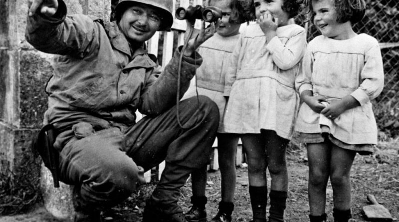 soldier shares his binoculars with three girls after the liberation of Normandy