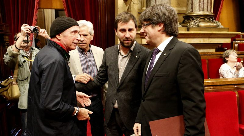 El president de la Generalitat, Carles Puigdemont, saluda el diputat de JxSí Lluís Llach, al ple del Parlament del 26 d'abril de 2017.
