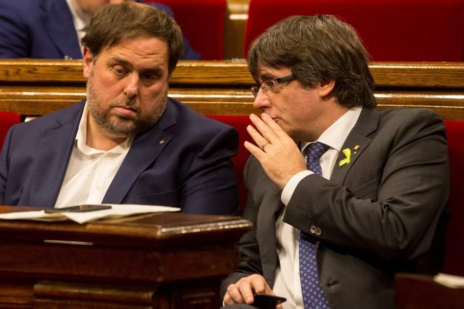 Puigdemont conversa con Junqueras durante una sesión del Parlamento catalán