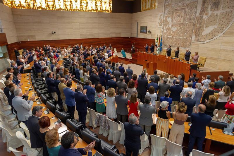 Los asistentes al acto institucional en la cámara Legislativa extremeña de pie escuchando el himno de Extremadura.