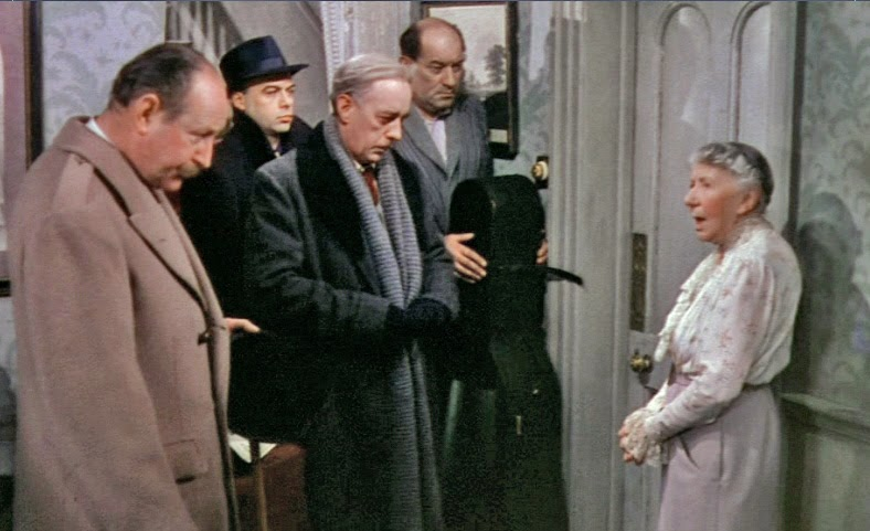 La señora Wilberforce, una venerable anciana que alquila dos habitaciones al misterioso profesor Marcus y a los cuatro miembros de su siniestra banda de música. Toda una metáfora del quinteto de la traición