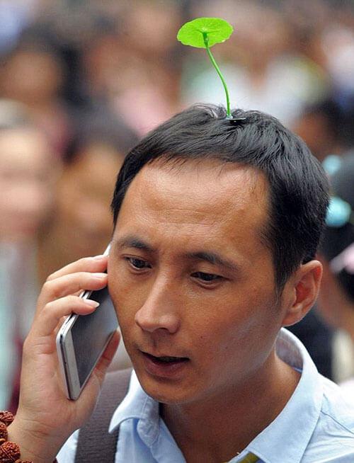 Chinees met een plantje op zijn hoofd
