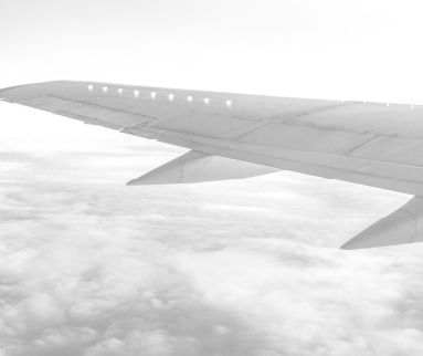 View looking over left wing of an airplane whilst airborne.