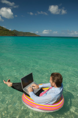stock-photo-8563526-relaxed-businessman-typing-blank-laptop-tropical-water