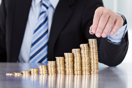 Close-up Of Businessman Stacking Coins