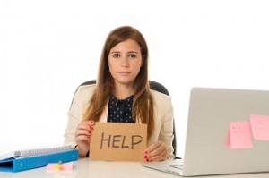 desperate businesswoman in stress at office computer holding help sign
