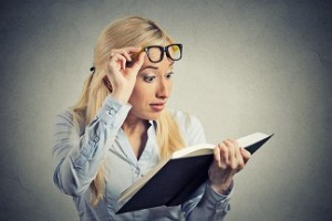 woman with glasses reading book shocked surprised