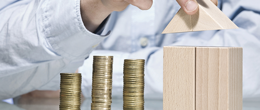 Person building house with building bricks beside stack of coins © REX/Shutterstock