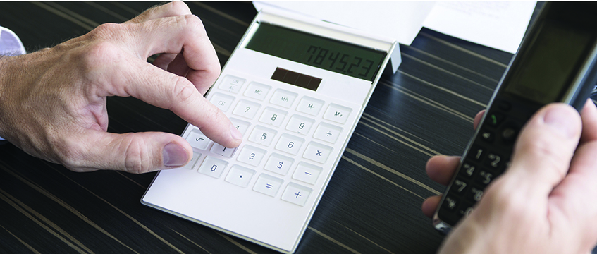 Man using calculator while on phone