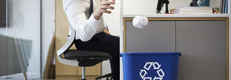 office worker throwing paper in recycling bin