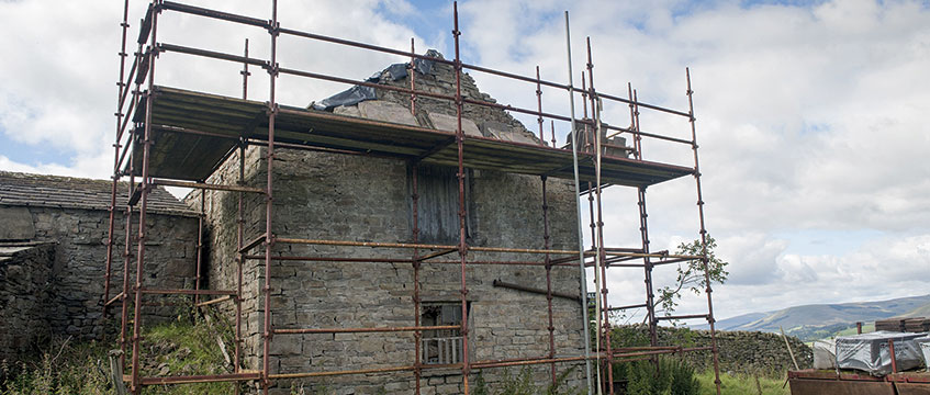 Stone barn with scaffolding