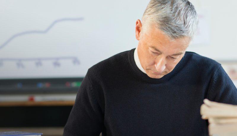 Teacher grading homework in classroom