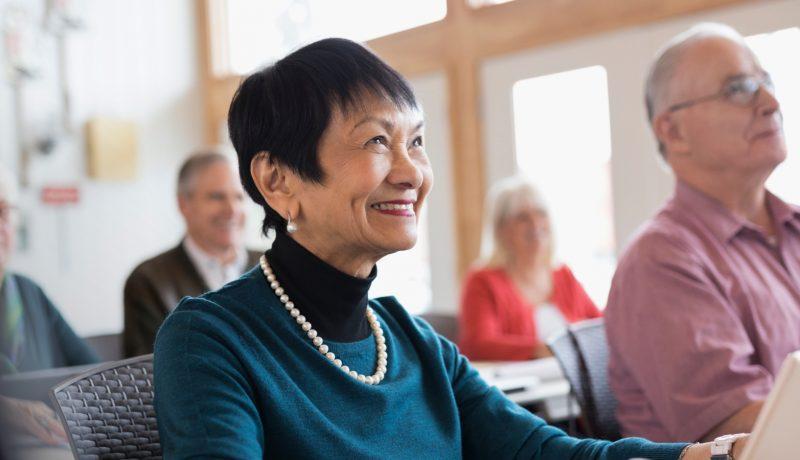 Smiling senior woman using digital tablet in classroom