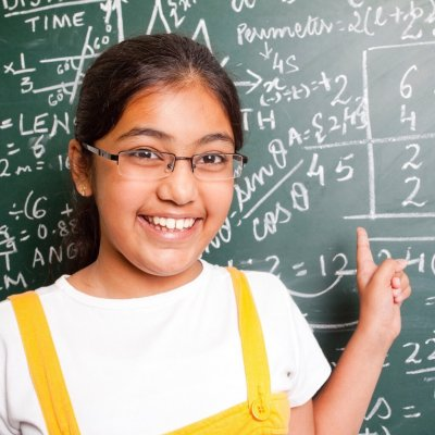 A smiling girl with glasses, pointing at a blackboard covered in text