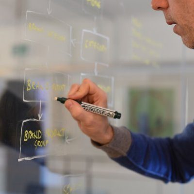 A man drawing a user journey on glass