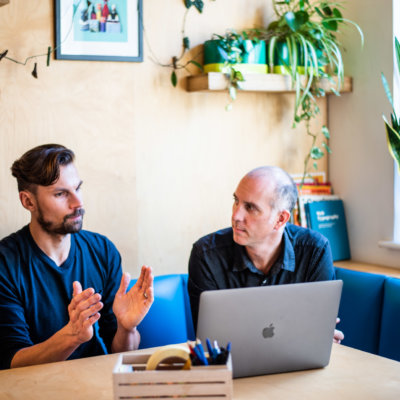 Two men around a table discussing client work