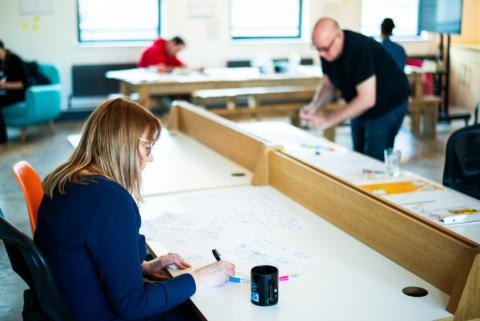 Four people working through design sprint exercises at desks