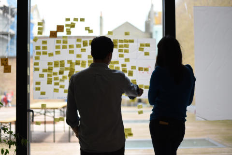 Two people having a discussion in front of a wall of post-it notes.