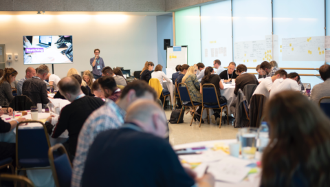 Chris running a design sprint workshop in a large glass room at UX London