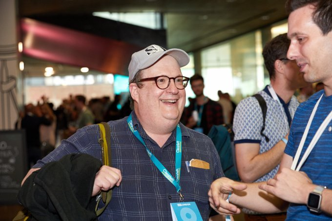UX London Jared Spool talking to an attendee in the busy foyer