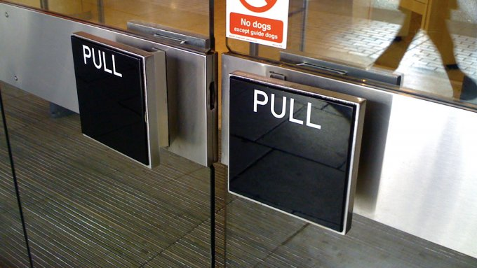 A door handle with a pushable affordance labelled with the word pull.