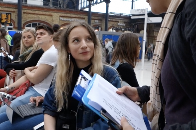 A commuter in a railway station being asked to participate.