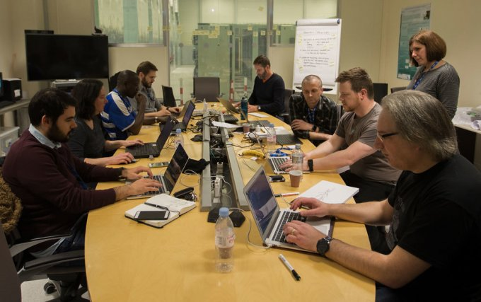 Gathered at CERN, hunched over laptops.