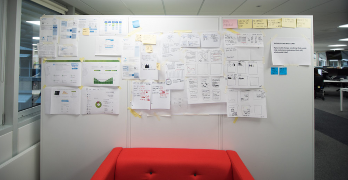 Display board covered in design sketches and customer journey maps