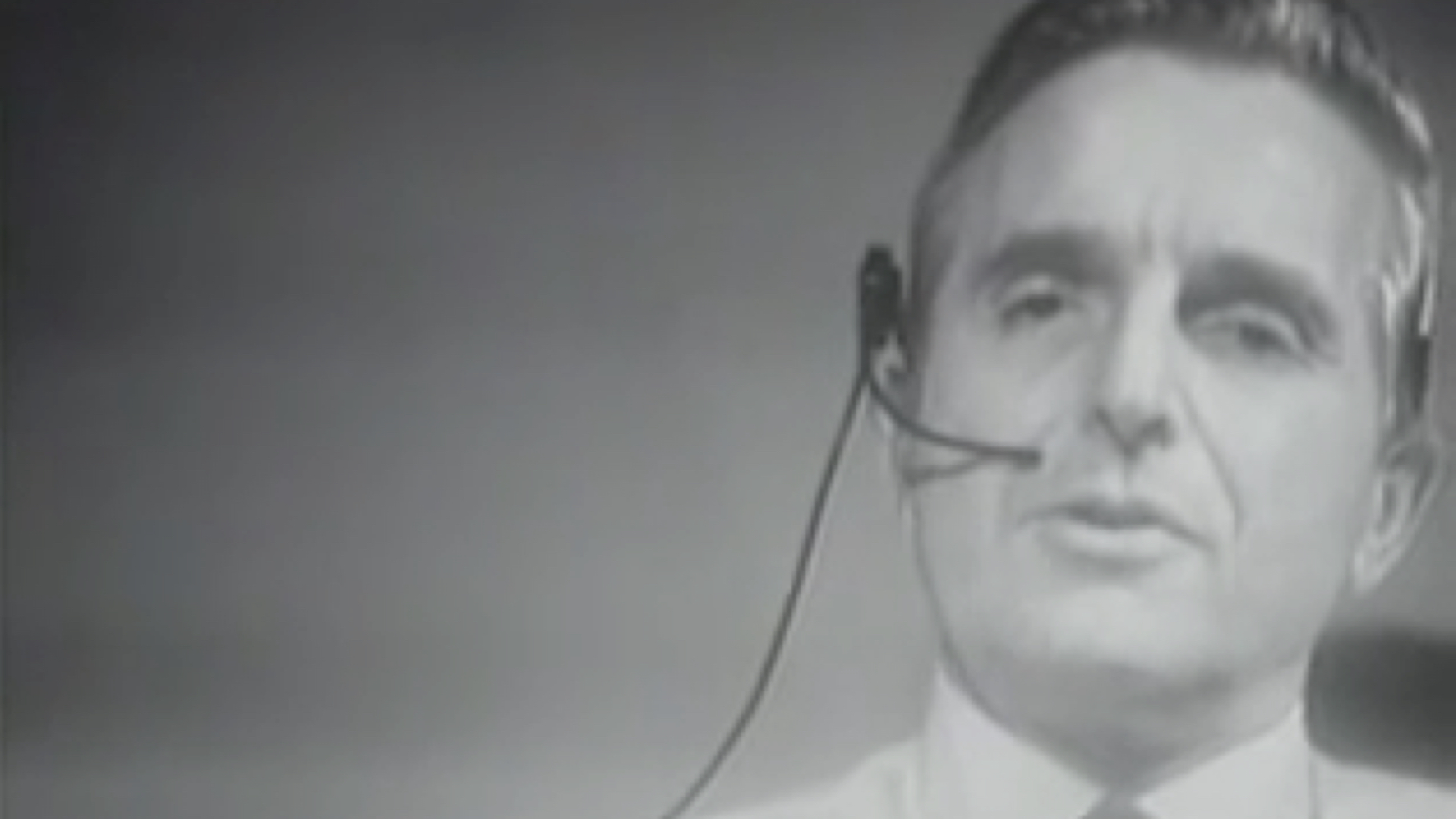 A screenshot from The Mother Of All Demos showing Douglas Engelbart wearing a headset.