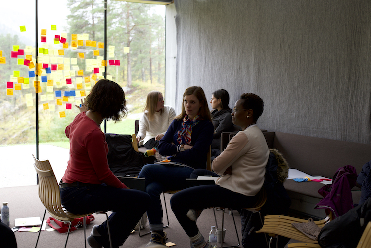 Group sat in front of a glass wall of post-its talking